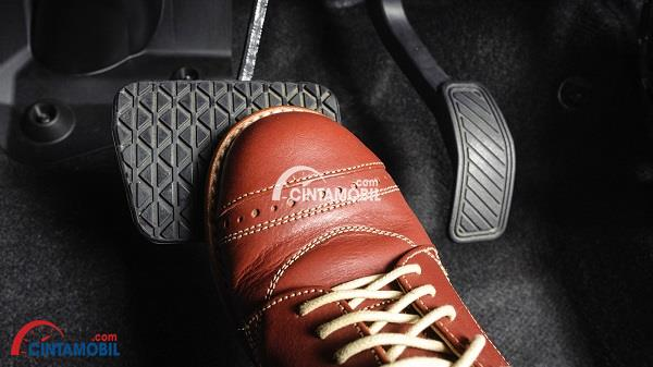 Sepatu berwarna coklat yang sedang menekan pedal rem pada mobil