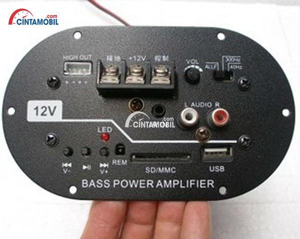Sebuah tangan yang memegang sistem subwoofer dan amplikasi sistem audio