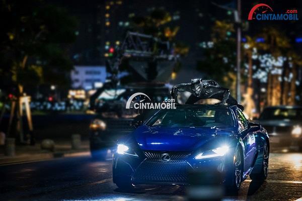 Seorang berkostum Black Panther sedang berada di atas Lexus LC 500