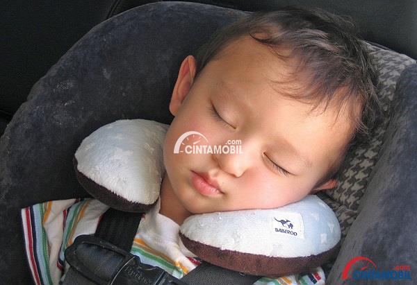 Seorang anak yang sedang tertidur di dalam mobil menggunakan bantal leher