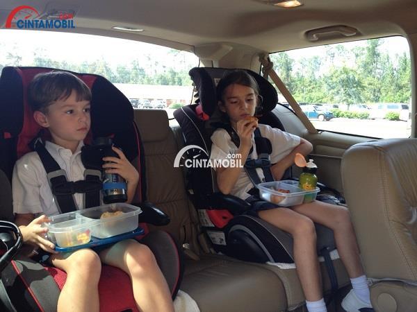 Dua orang anak laki-laki yang sedang makan di dalam mobil