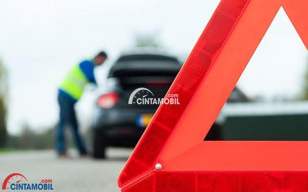 Gambar segitiga pengaman dengan seseorang yang sedang berdiri di samping mobil sebagai background