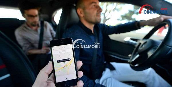 Seorang pengemudi Uber dengan penumpang dan smartphone yang menunjukan aplikasi Uber