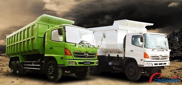 Mobil truk buatan Hino yang berwarna putih dan hijau dengan latar belakang bukit
