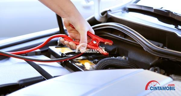 Gambar yang memperlihatkan tangan yang memegang kabel jumper berwarna merah
