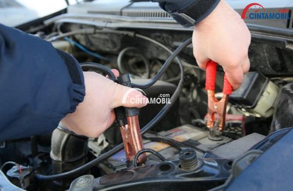 Gambar yang memperlihatkan tangan yang sedang menyetrum baterai mobil menggunakan kabel jumper