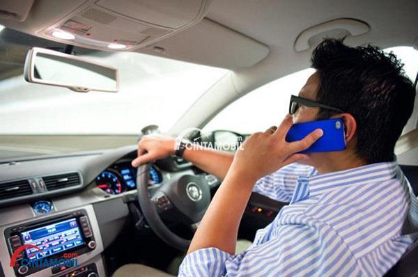 Seorang pengemudi pria berkemeja putih yang sedang menelpon
