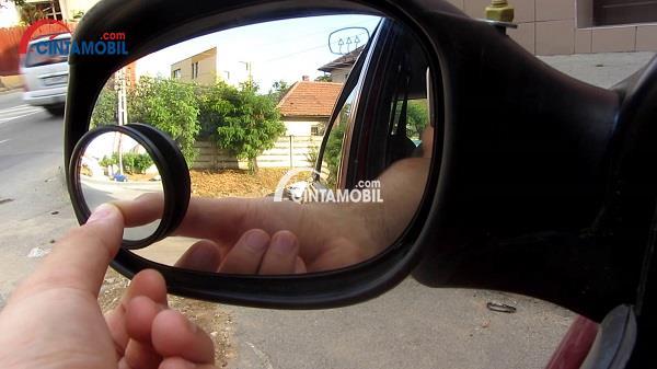 Gambar yang memperlihatkan cermin blind spot yang dipasang pada kaca spion samping mobil