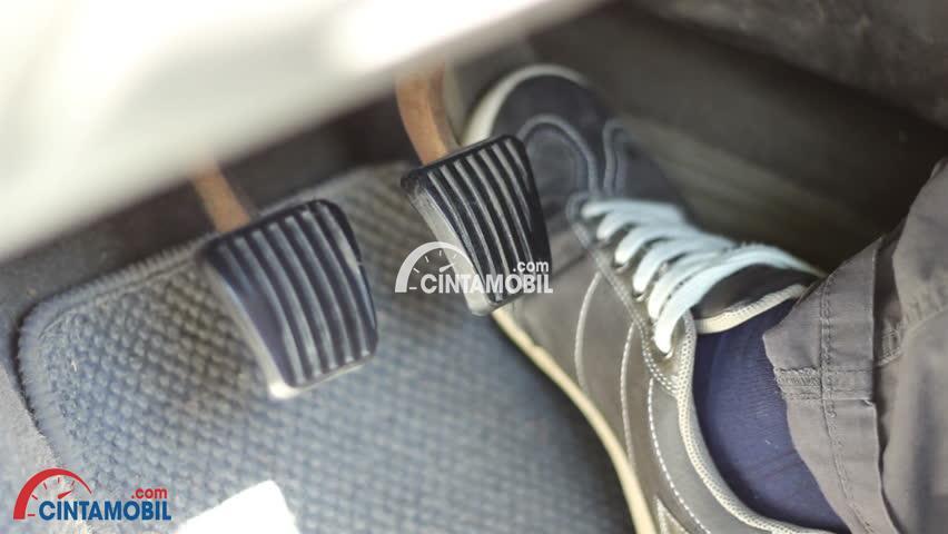 Gambar yang memperlihatkan kaki pengendara mobil yang sedang menekan rem