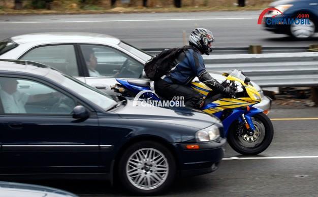 Gambar yang memperlihatkan pengendara motor yang ingin menyalip mobil