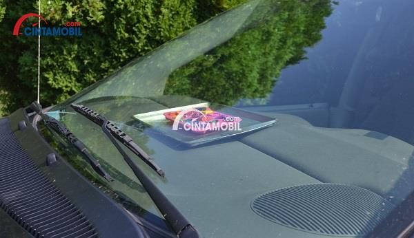 Gambar yang menunjukan krayon yang berada di bagian dashboard mobil