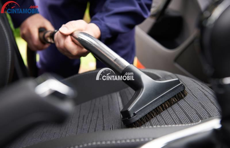 Gambar yang menunjukan tangan yang sedang membersihkan jok mobil dengan vacuum cleaner