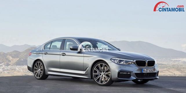 Mobil BMW Seri 5 yang sedang berada di atas jalan dengan background pemandangan gunung