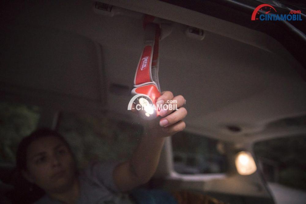 Gambar yang menunjukan seorang wanita sedang memasang lampu pada bagian dalam mobil