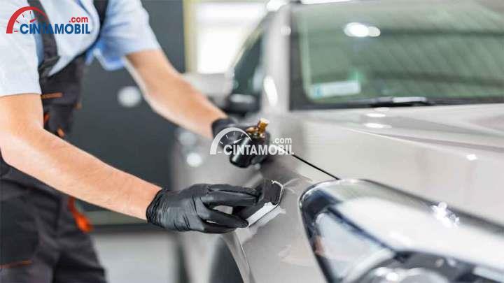 Gambar yang menunjukan teknisi yang sedang memberikan lapisan pelindung pada mobil