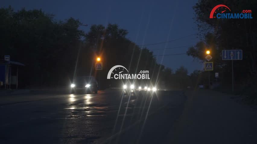 Gambar yang menunjukan mobil yang sedang melaju di malam hari