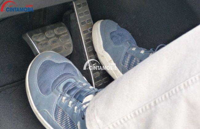 gambar pengemudi menginjak pedal rem dengan kaki kiri dan pedal gas dengan kaki kanan