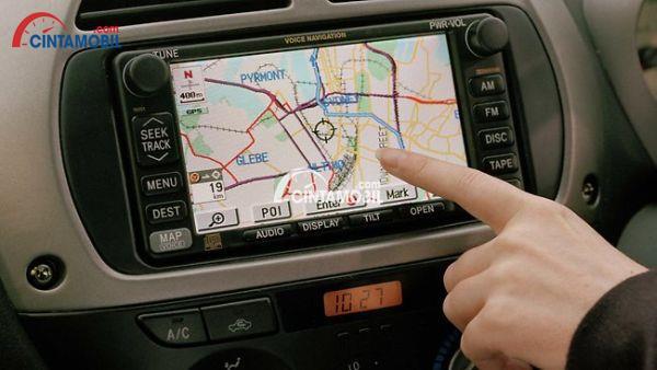 Gambar yang menunjukan sebuah tangan sedang menunjukan suatu tempat pada sebuah GPS