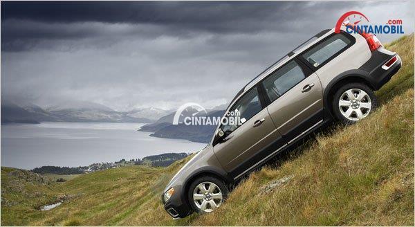 Gambar yang menunjukan sebuah mobil berwarna silver sedang menuruni tebing yang curam