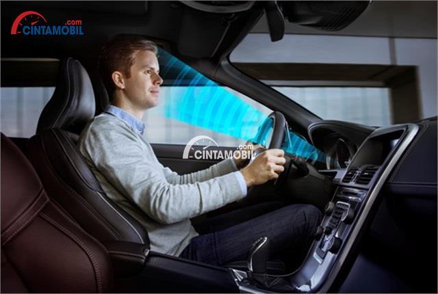 Gambar yang menunjukan sistem yang mengalisa muka seorang pengemudi pria di dalam sebuah mobil