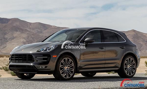 Gambar yang menunjukan mobil Porsche Maca berwarna hitam yang berada di padang pasir
