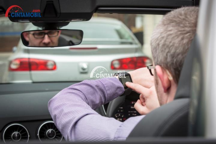 Gambar yang menunjukan seorang pengemudi sedang memeriksa jam tangan ketika sedang berkendara