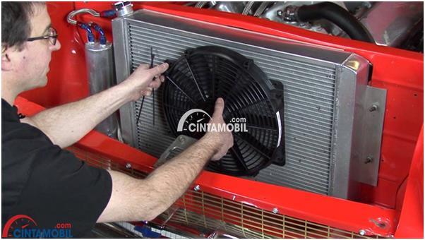 Gambar yang menunjukan mekanik yang sedang mengganti kipas radiator pada mobil