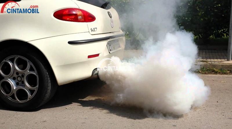Gambar yang menunjukan mobil berwarna putih yang mengeluarkan asap knalpot berwarna putih