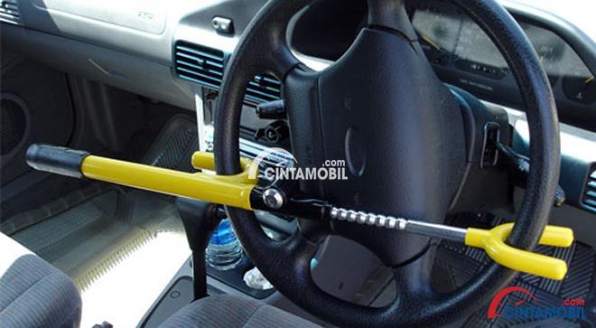 Gambar yang menunjukan kunci kemudi yang terpasang pada bagian kemudi mobil