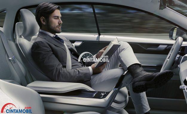 Gambar yang menunjukan seorang pengemudi pria sedang duduk pada sebuah mobil otonom