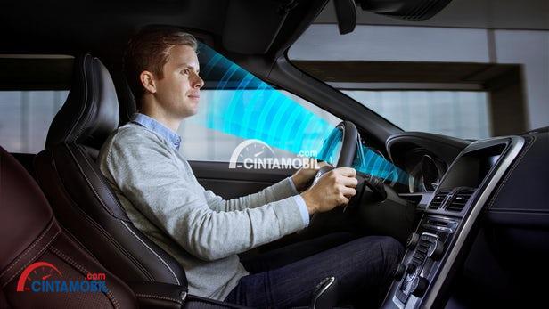 Gambar yang menunjukan seorang pengemudi yang sedang dipindai oleh sebuah sensor yang ada pada mobil