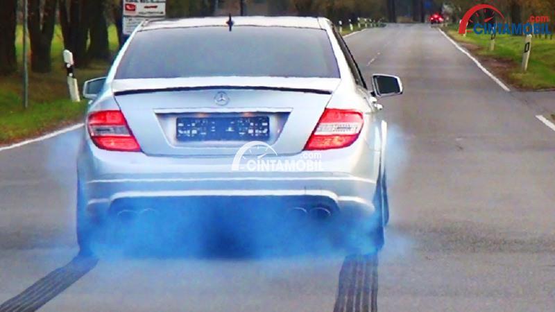 Gambar yang menunjukan mobil yang mengeluarkan asap berwarna biru pada knalpotnya