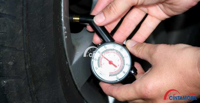 Gambar yang menunjukan tangan yang sedang melakukan pengecekan tekanan ban