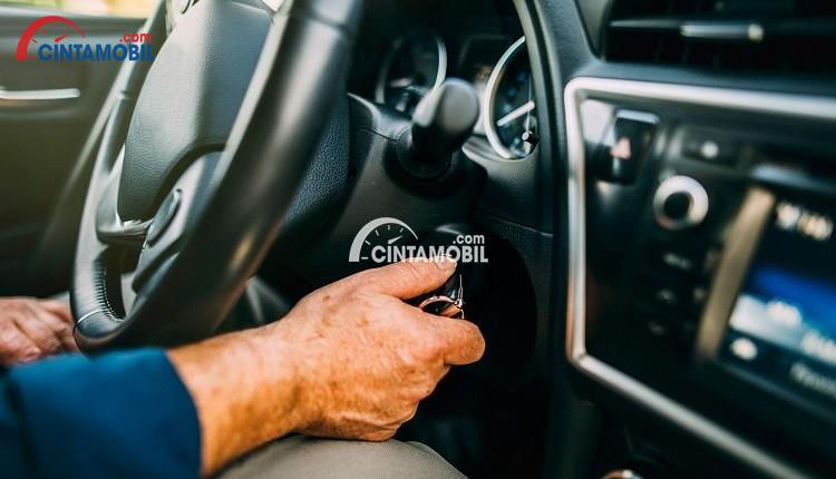 Gambar yang menunjukan tangan yang sedang memutar kunci untuk menghidupkan mobil