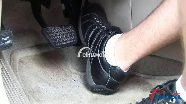 Gambar yang menunjukan kaki pengemudi yang sedang menekan pedal gas mobil