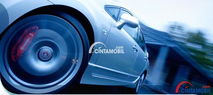 Gambar yang menunjukan bagian rem pada ban depan mobil yang sedang melaju