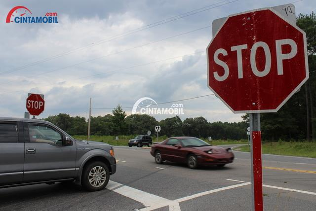 Gambar yang menunjukan persimpangan dengan papan rambu lalu lintas mengatakan stop