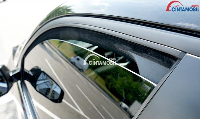 Gambar yang menunjukan mobil yang menurunkan jendela samping sedikit untuk sirkulasi udara