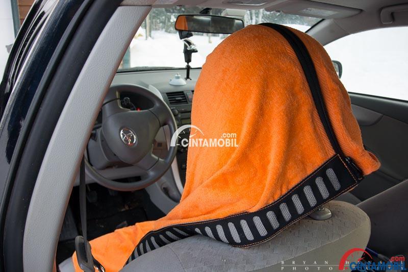 Gambar yang menunjukan handuk yang terletak pada bagian kepala kursi pengemudi pada mobil