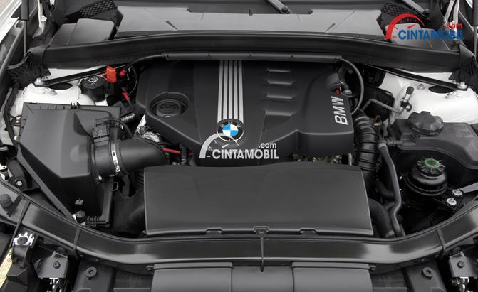 Gambar yang menunjukan sistem mesin pada bagian kap mesin dengan logo BMW ditengah mesin