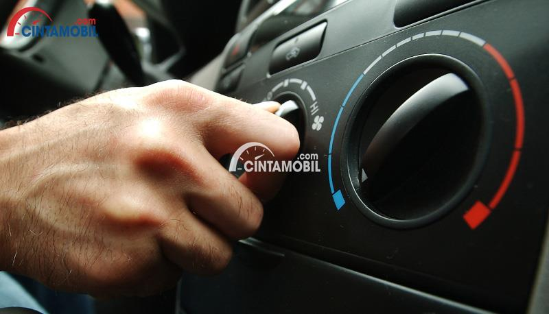 Gambar yang menunjukan tangan pengemudi yang sedang memutar bagian AC pada dashboard mobil