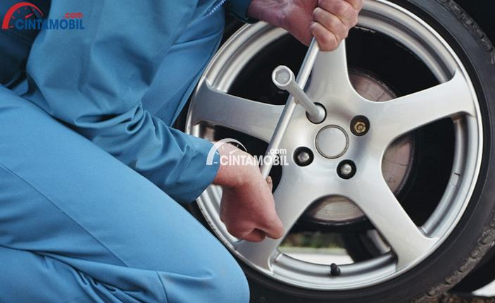 Gambar yang emnunjukan seorang montir yang sedang membuka ban sebuah mobil