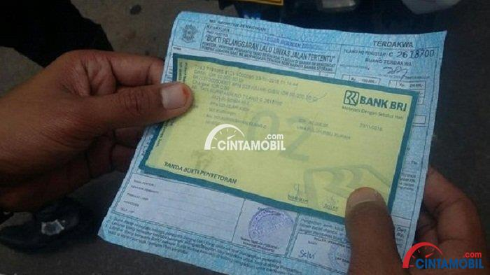 Gambar yang menunjukan surat tilang dari polisi dengan kertas dari bank BRI