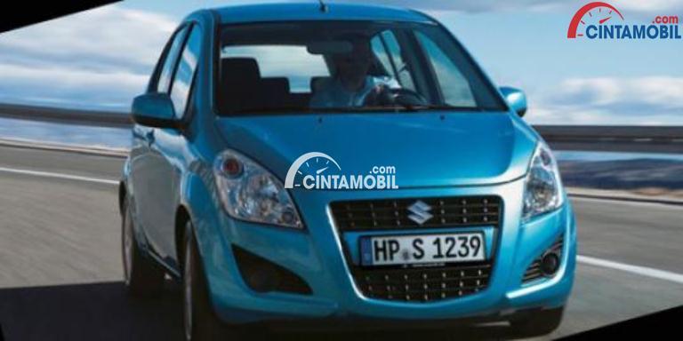 Gambar mobil Suzuki Splash 2013 berwarna biru dilihat dari sisi depan sedang berlaju di jalan