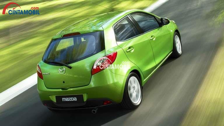 Mobil Madzda 2 2012 berwarna hijau silihat dari sisi belakang sedang di jalan naik gunung