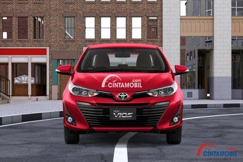 Gambar mobil Toyota Vios 2018 berwarna merah dilihat dari sisi depan sedang berjalan di jalan