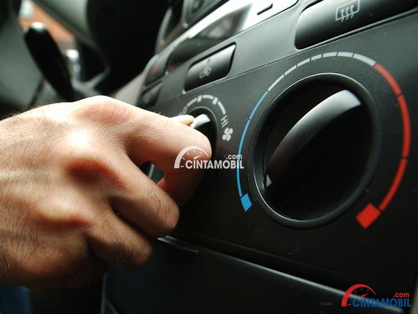 Gambar yang menunjukan tangan yang sedang menghidupkan AC mobil