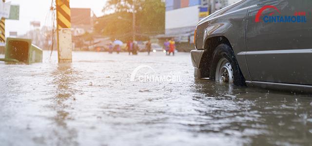 Gambar yang menunjukan ban mobil yang sedang terendam banjir
