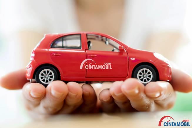 Gambar yang menunjukan mobil mainan berwarna merah yang berada ditangan