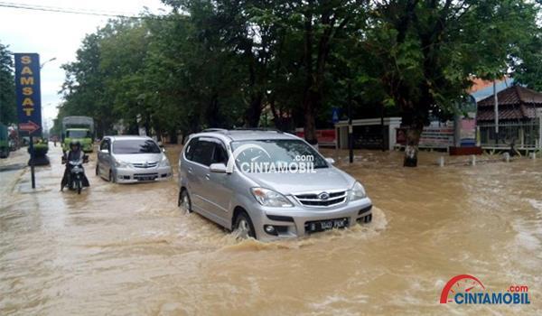 gambar sebuah mobil melewati genangan banjir